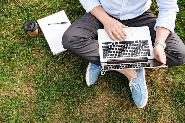 Caucasian man in formal business clothing, sitting on grass in park while working on silver laptop