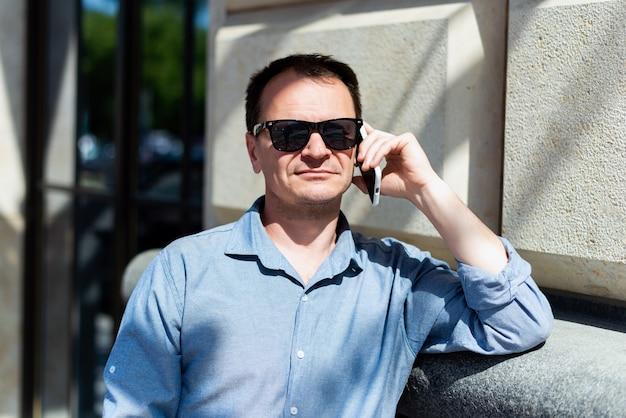 Кавказский мужчина сорок лет бизнесмен в городе летом разговаривает по телефону.