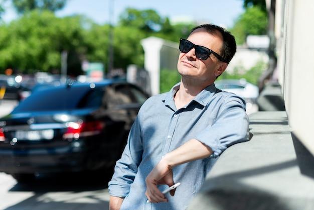 Кавказский мужчина сорока лет бизнесмен возле здания в солнцезащитных очках отдыхает.