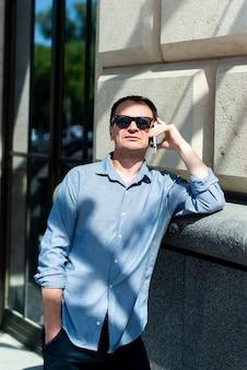 Кавказский мужчина сорока лет бизнесмен возле здания разговаривает по телефону.