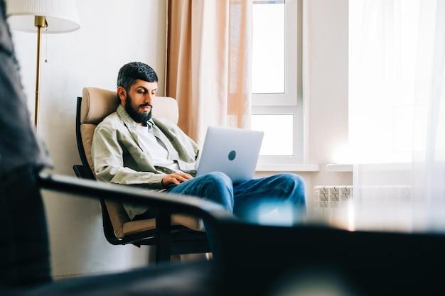 自宅で働いて、肘掛け椅子に座って、ラップトップコンピューターを使用している白人男性のフリーランサー。