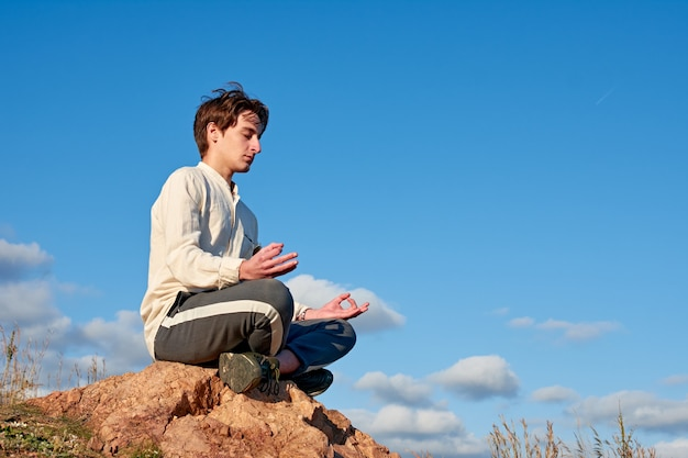 A caucasian man from spain sitting on a rock and meditating in grassy and disconnected area