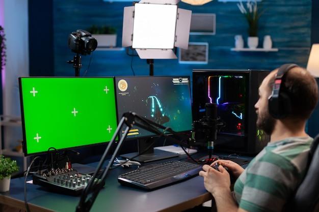 녹색 화면 디스플레이가 있는 강력한 전문 컴퓨터에서 온라인 비디오 게임을 스트리밍하는 백인 남자 게이머. 사수 게임을 하는 크로마 격리 데스크탑을 조롱하는 pc를 사용하는 스트리머