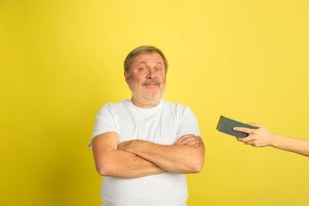 Uomo caucasico che ottiene un regalo emozionante isolato su colore giallo