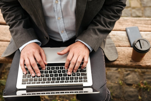 Caucasian man in gray classical suit, sitting on bench in park with takeaway coffee while typing on silver laptop