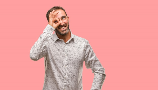 Caucasian man on grey brackground confident doing ok gesture on eye