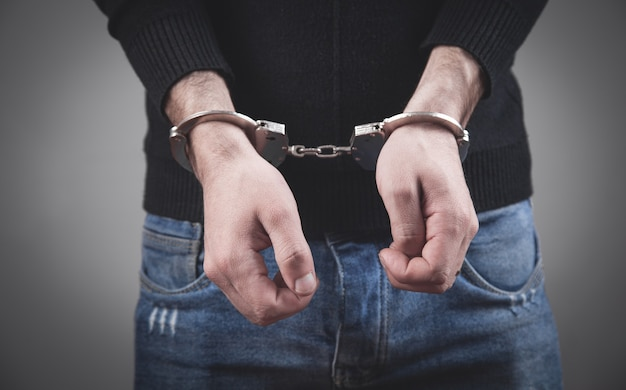 Caucasian man hands in handcuffs.