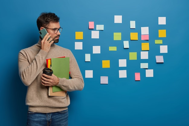 Caucasian man has creative approach to organizing work, leaves colorful stickers on wall, discusses working schedule with partner via smartphone