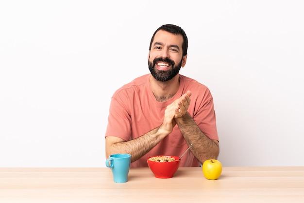 Кавказский мужчина завтракает за столом и аплодирует после выступления на конференции.