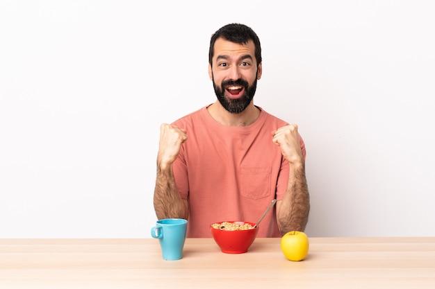 勝者の位置で勝利を祝うテーブルで朝食を持っている白人の男。