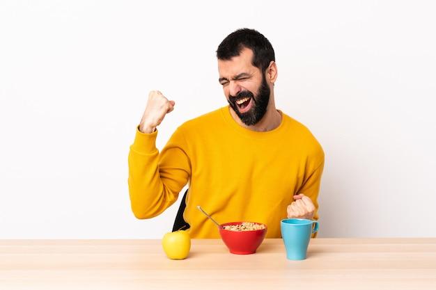 勝利を祝うテーブルで朝食を持っている白人の男。