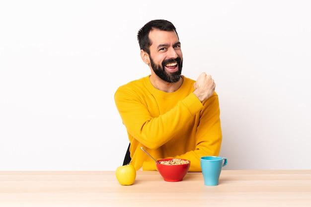 Кавказский мужчина завтракает за столом, празднует победу.
