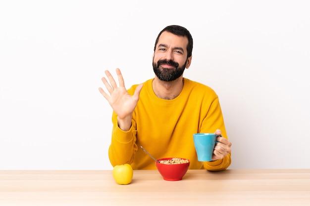 손가락으로 5 세 테이블에서 아침을 먹고 백인 남자.
