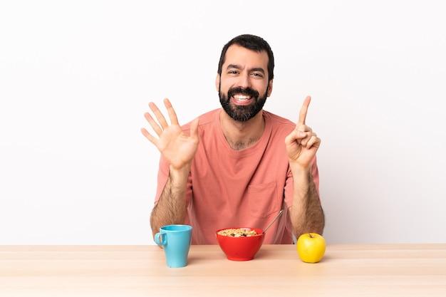Кавказский мужчина завтракает в таблице, считая шесть пальцами.