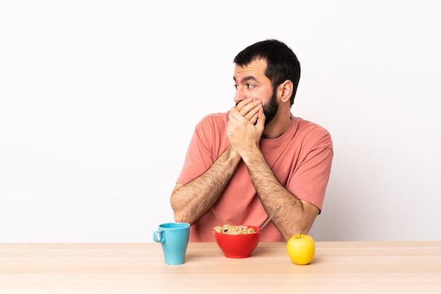 口を覆い、横を向いているテーブルで朝食をとっている白人男性。