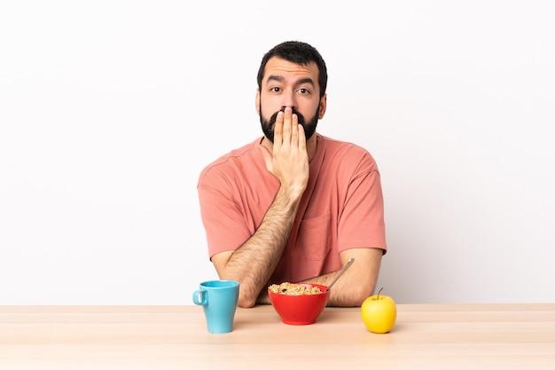手で口を覆うテーブルで朝食をとっている白人男性。