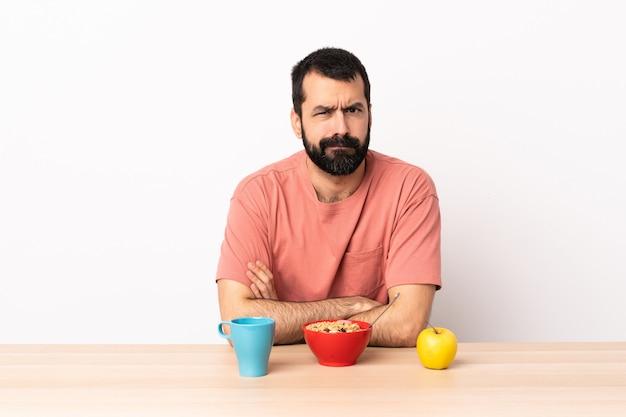 動揺してテーブルで朝食を持っている白人の男。