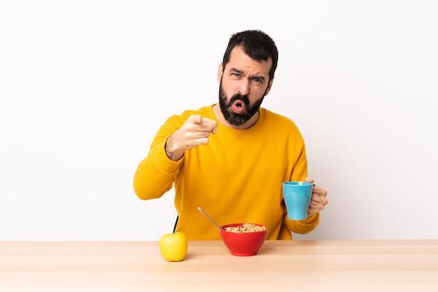 Кавказский мужчина, завтракающий за столом, разочарован и указывая на фронт.