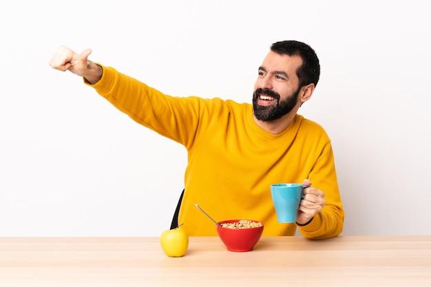 백인 남자 제스처를 엄지 손가락을주는 테이블에서 아침 식사.