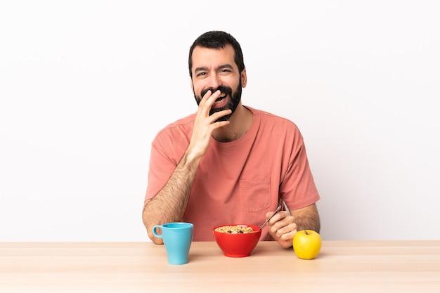 Кавказский человек, завтракающий в столе, счастливый и улыбается, прикрывая рот рукой.