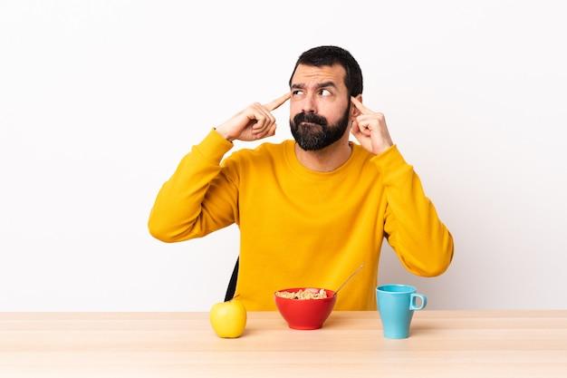 Кавказский человек завтрака в таблице, имея сомнения и мышления.