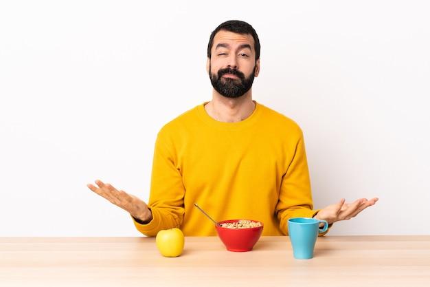 疑いを持ってテーブルで朝食をとっている白人男性。