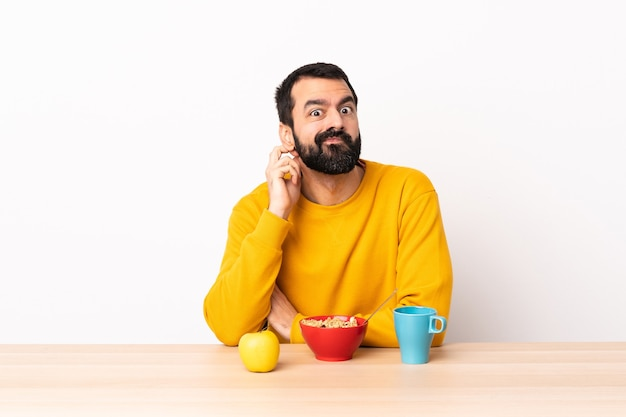 Кавказский мужчина завтракает в столе, сомневаясь.