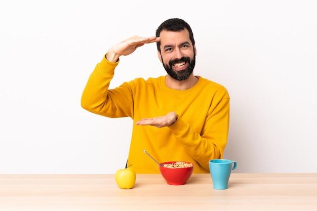 백인 남자는 광고를 삽입하려면 copyspace 들고 테이블에서 아침 식사.