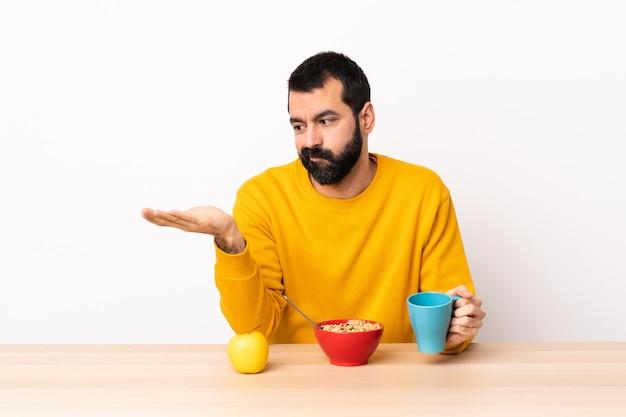 疑問を持つcopyspaceを保持しているテーブルで朝食を持っている白人の男。