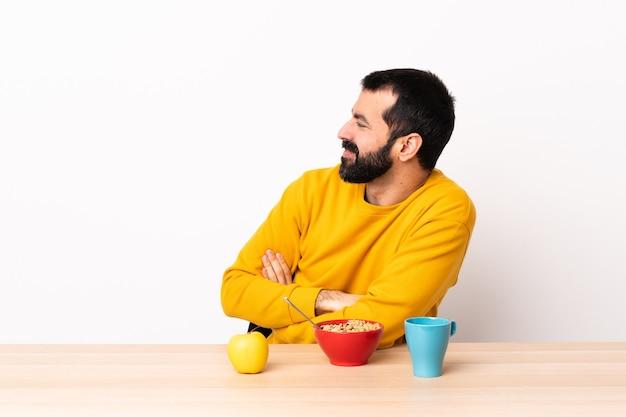 横向きのテーブルで朝食をとっている白人男性。