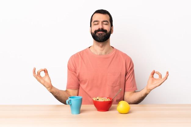 禅のポーズでテーブルで朝食をとっている白人男性。
