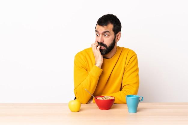 Кавказский мужчина, завтракающий за столом, немного нервничает.