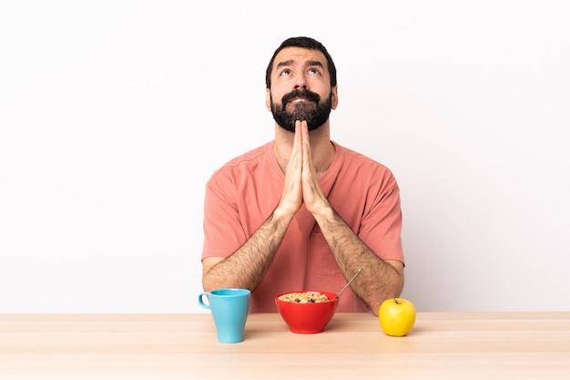 テーブルで朝食をとっている白人男性は、手のひらを一緒に保ちます。人は何かを求めます。