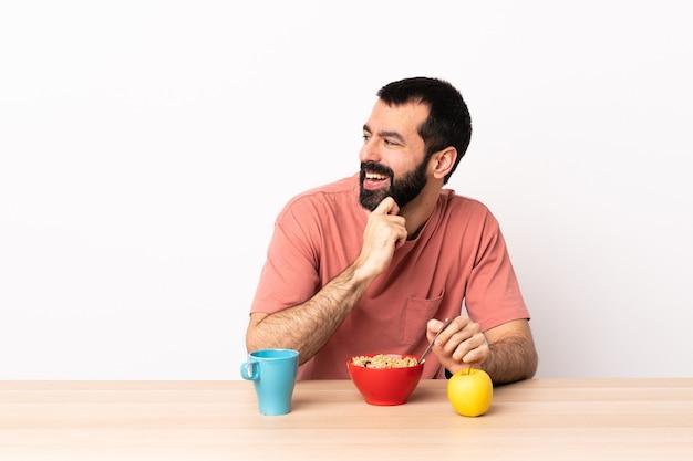 Кавказский мужчина завтракает в столе, глядя в сторону и улыбается.
