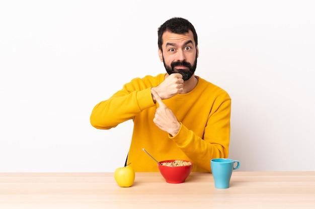Кавказский мужчина завтракает за столом, делая жест опоздания.