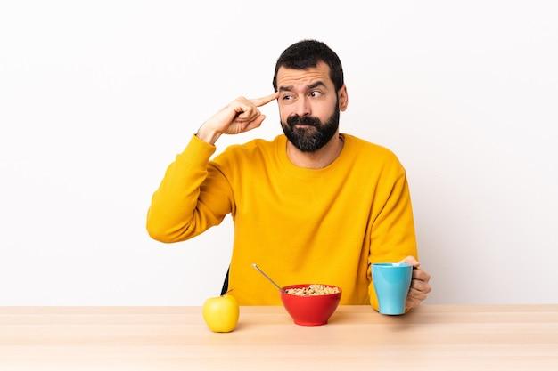 Кавказский мужчина завтракает за столом, делая жест безумия, положив палец на голову