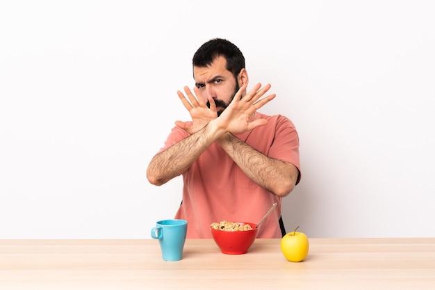 Кавказский мужчина завтракает в нервном столе, протягивая руки вперед.