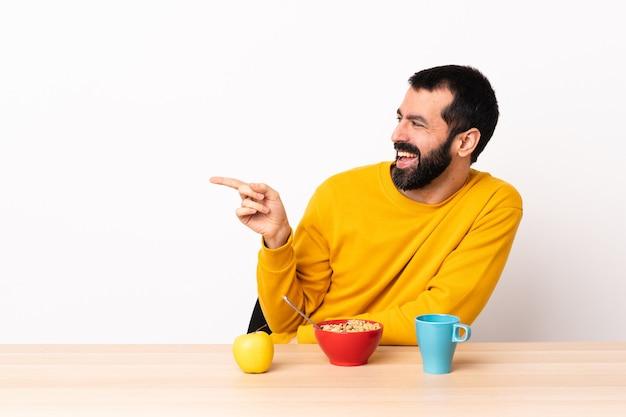 指を横に向けてテーブルで朝食をとり、製品を提示する白人男性。