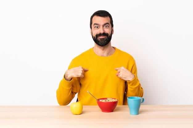 自分を指してテーブルで朝食をとっている白人男性。