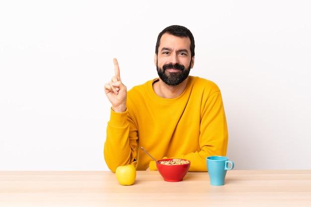 素晴らしいアイデアを指し示すテーブルで朝食をとっている白人男性。