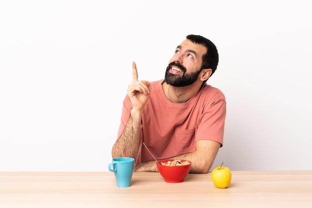 Кавказский мужчина за завтраком в столе, указывая на прекрасную идею.