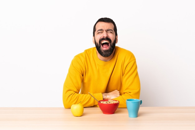 백인 남자 입 벌리고 앞에 외치는 테이블에서 아침 식사.