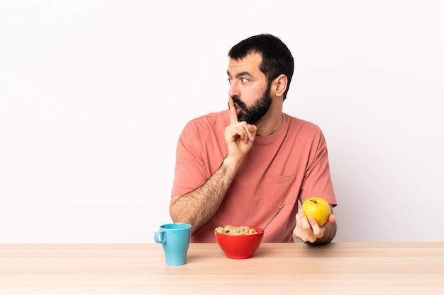 口の中に指を入れて沈黙ジェスチャーの兆候を示すテーブルで朝食を持っている白人の男