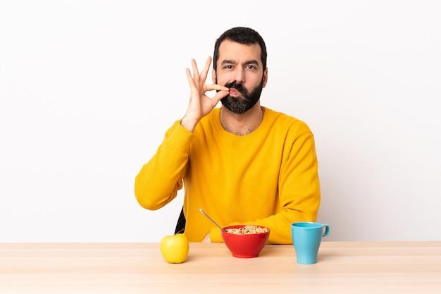 沈黙のジェスチャーの兆候を示すテーブルで朝食を持っている白人の男