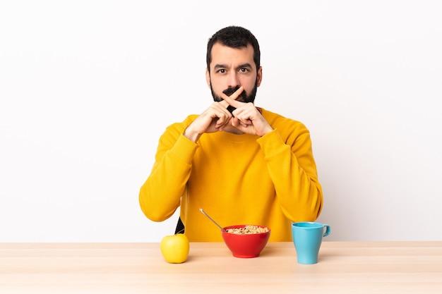 백인 남자 침묵 제스처의 기호를 보여주는 테이블에서 아침 식사.