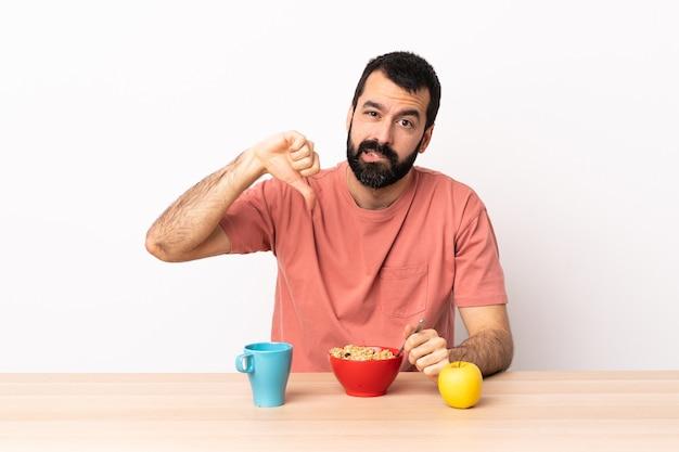 否定的な表現で親指を下に示すテーブルで朝食をとっている白人男性。