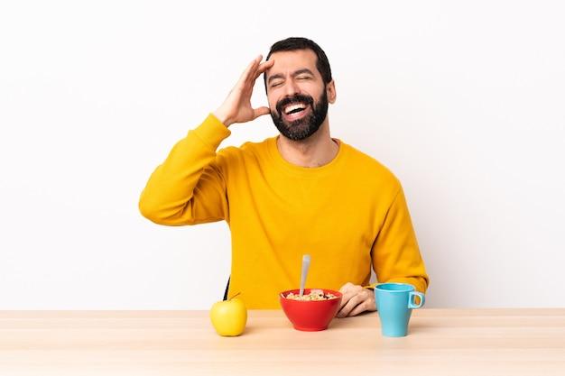 Кавказский человек, завтракающий в столе, много улыбается.