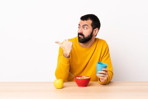 不幸なテーブルで朝食を持っていると側を指している白人の男