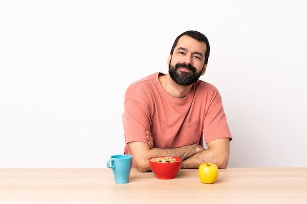 腕を組んでテーブルで朝食をとる白人男性が楽しみにしています。