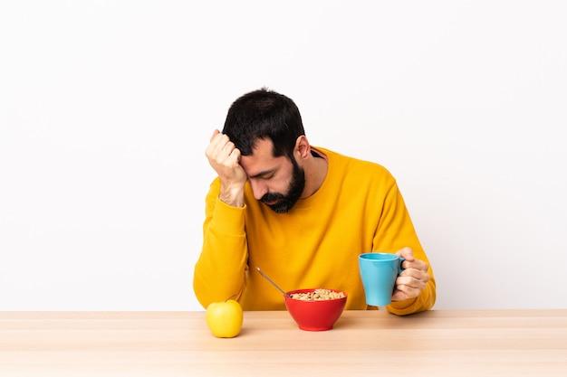 頭痛とテーブルで朝食を持っている白人の男